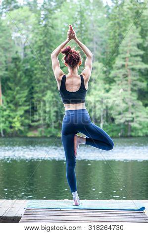 Beautiful Girl  Practicing Yoga Tree Pose, Vrikshasana   On The Lake.  The Concept Of Appeasement,