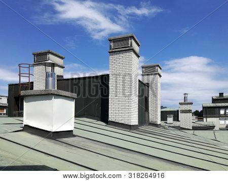 Chimneys And Vents On The Tin Roof Of The Building. A Chimney Is An Architectural Ventilation Struct