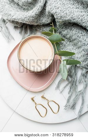 Golden Earrings And Coffee On Jewelry Plate With Beige Silk Cloth