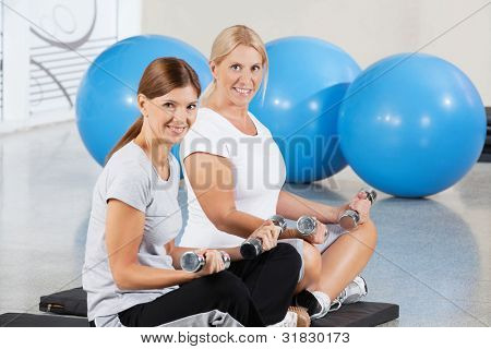 Two elderly women exercising with dumbbells on gym mats in fitness center