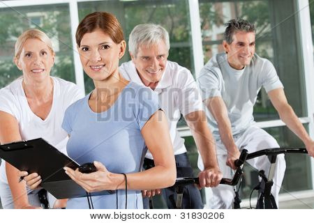Fitness trainer coaching spinning exercise class with seniors in gym