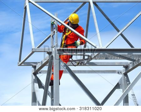 Man Working On The Working At Height. Professional Industrial Climber In Helmet And Uniform Works At