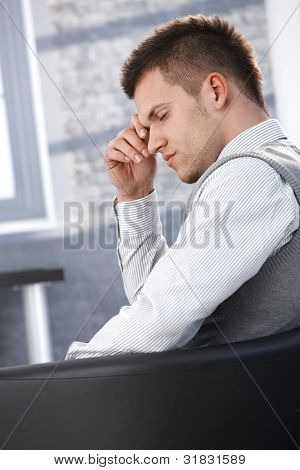 Businessman sitting in armchair eyes closed, taking a break.