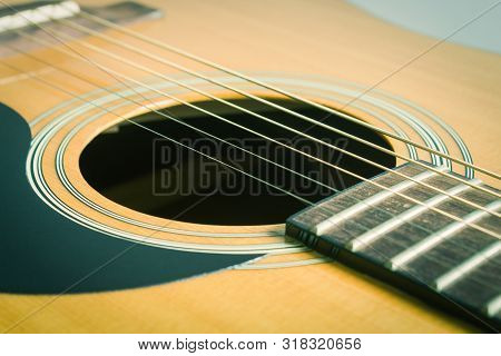 Sound Hole And Acoustic Guitar String And Pickguard And Fingerboard And Fret In Crosswise View