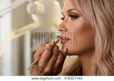 Beautiful Well-groomed Girl With Gorgeous Shiny Hair In Beauty Salon. Makeup Artist Draws Contour Of