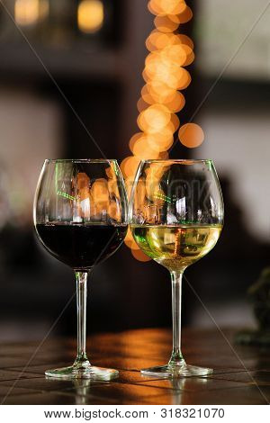 Two Glasses Of Wine White And Red Standing On A Table. Colorful Bokeh. Wine Tastings, Wine Tour. War