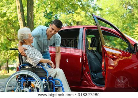 Young Man Helping Disabled Senior Woman In Wheelchair To Get Into Car Outdoors