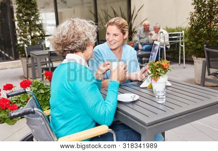 Nursing help with tablet computer talking to senior citizen in nursing home while having coffee