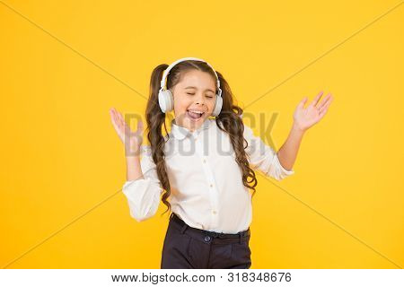 The Song Clicks With Her Mood. Adorable Little Girl Singing A Song On Yellow Background. Cute Small