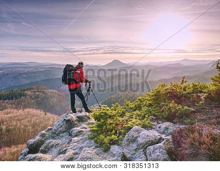 Photographer With Tripod In Hand. Man Hold Tripod, Stand On Rock. Hiker Admiring The Stunning Misty