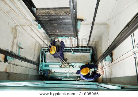 two machinist worker technicians at work adjusting lift with spanners in elevator hoistway