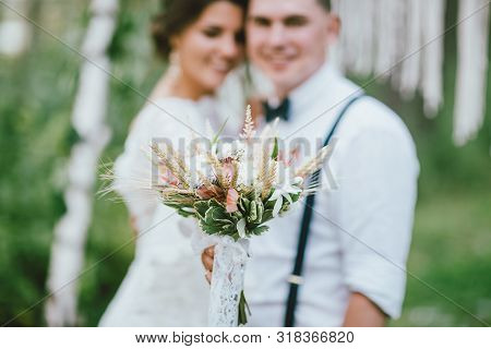 Happy Newly Married Couple With Boho Style Bouquet On Wedding Ceremony In The Forest. Selective Focu