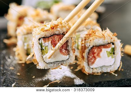 Macro shot of eating uramaki sushi rolls with cream cheese, salmon, tuna shavings or dried bonito, cucumber, nori. Taking portion of fresh katsuobushi roll in Japanese restaurant closeup