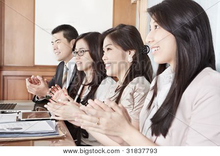 A group business people clapping their hand while on meeting in the office