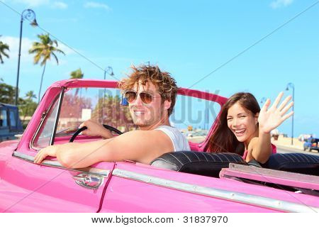 poster of Couple happy in vintage retro convertible car. Friends driving on summer road trip in pink car. Beautiful young Caucasian man and Asian woman smiling joyful on sunny summer day traveling.