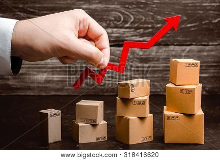 Businessman Holds A Red Arrow Up Above Cardboard Boxes Folded Incrementally. Increase Sales And Prod