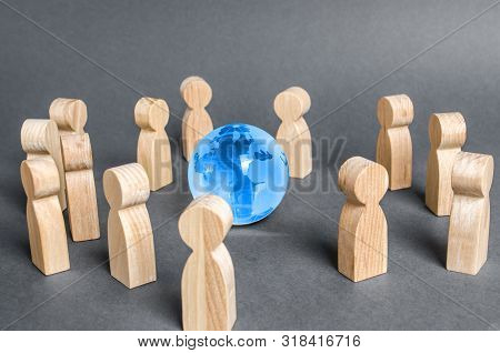 People Surrounded A Globe World Planet Earth. Cooperation And Collaboration Of People Around The Wor