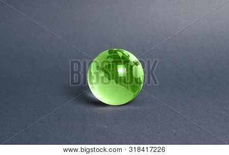 Green Glass Planet Globe On A Gray Background. International Diplomacy. Foreign Languages. Globaliza