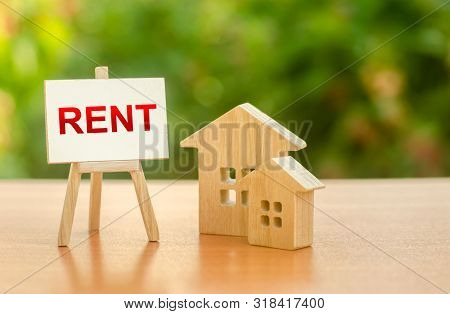 Two Figures Of Houses And An Easel With The Word Rent. The Concept Of Temporary Rental Housing And R