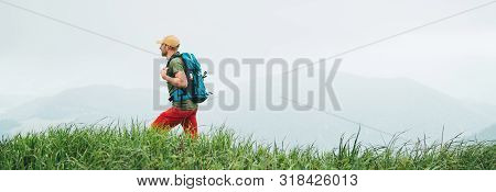 Side Shot Of Hiker Man Walking By The Foggy Cloudy Weather Mountain Range Path With Backpack. Active