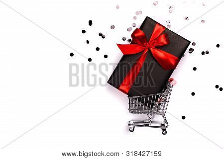 Gift Box With Red Bow In A Metal Shopping Basket With Place For Text.
