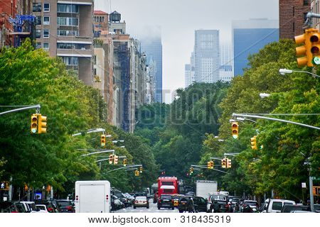 Manhattan Buildings Skyline From 5th Ave. Harlem In A Foggy Day, Through The Trees And Traffic Light