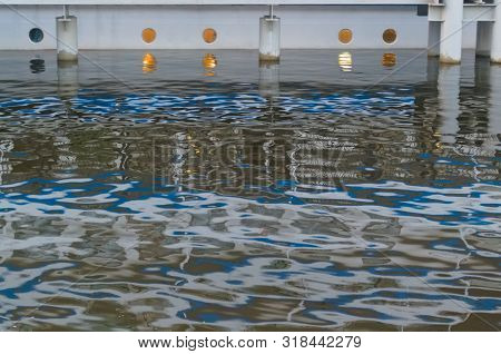 Broken Reflection. Reflection Of A River Boat Standing At The Pier. Portholes On The Lower Deck Are