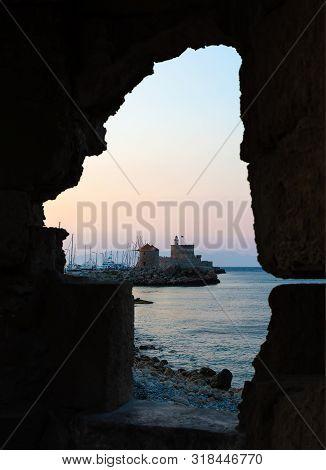 Agios Nikolaos Fortress On The Mandraki Harbour Of Rhodes Greece. View Through The Embrasure. Sunset