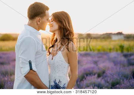 Sensual Couple In Lavender Field Romantic Time. Beautiful Young People Hug, Kiss Outdoor Medium Shot