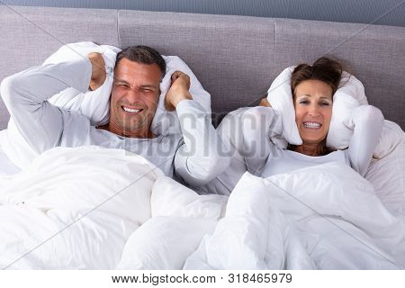 Mature Couple Disturbed By Noise Covering Their Ears With Pillow On Bed