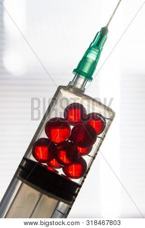 Medical Syringe Filled With Red Capsules With Retinol Vitamins Acetate