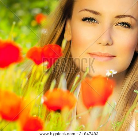 Closeup on beautiful woman face, female enjoying flower field, lovely girl at spring outdoor vacation, nice model relaxing at floral poppy garden, gorgeous model over natural bakground