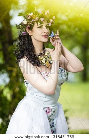 Portrait Smiling Sensual Brunette Female in White Dress Outdoors. Posing with Flowery Chaplet and Butterfly Against Sunlight.Vertical Image poster