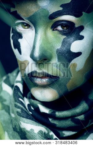 Beautiful young fashion woman with military style clothing and face paint make-up, khaki colors, halloween celebration poster