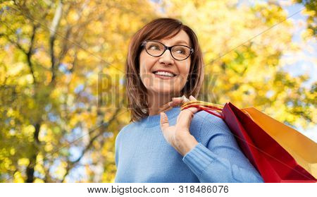 sale and old people concept - smiling senior woman in glasses with shopping bags over autumn park background