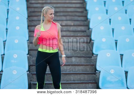 young caucasian fitness woman is standing at stadium