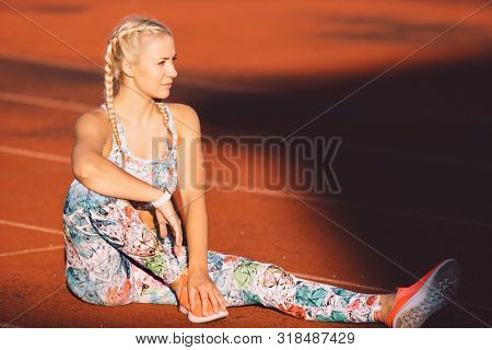 young caucasian fitness woman resting at stadium on a sunny day