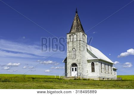 The Historic Immanuel Lutheran Church In Admiral, Saskatchewan With A Canola Field In The Background