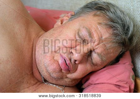Unshaven Senior Man Sleeps On Bed On Pillow And Snores.  Close-up Portrait. Indoors.