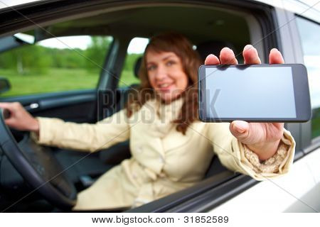Beautiful woman sitting in a car and showing her smartphone out the window