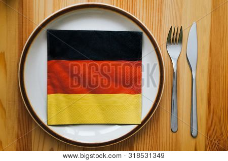 Plate And Serviette With A German Flag Pattern Lying On A Wooden Table. Fork And Knife, Cutlery. Ger