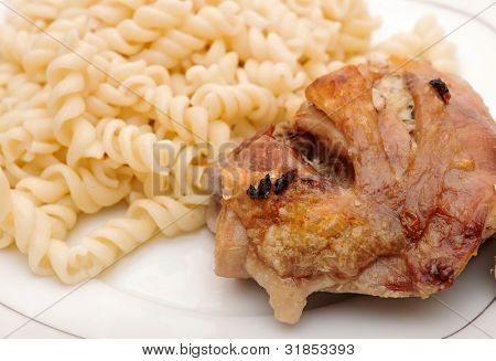 A plate of pasta and chicken with garlic on wood background