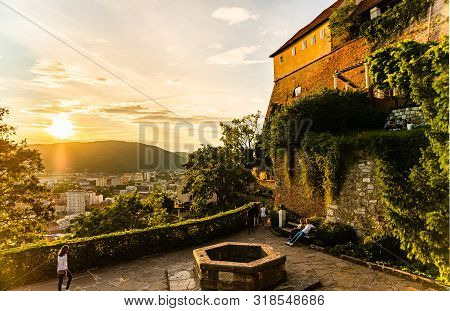 Graz, Austria - 17.08.2019 : View At Famous Castle At Schlossberg Hill And Wish Well. Above Graz Cit
