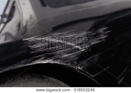 Damaged Car Body After A Crash Accident. Black Vehicle Wheel Arch Closeup. Scratches And Dents. Repa