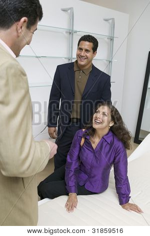 Couple Examining Mattress With Salesman
