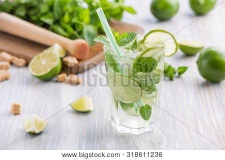 Glass of non-alcoholic mojito on a wooden table and ingredient on the background. Mojito refreshing cocktail. Summer cocktail. Summer mojito.
