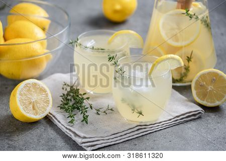 Summer lemonade with thyme and pieces of ice in a transparent glass. Refreshing cocktail. Cold drink with lemon and thyme. Refreshing summer drink. Citrus lemonade