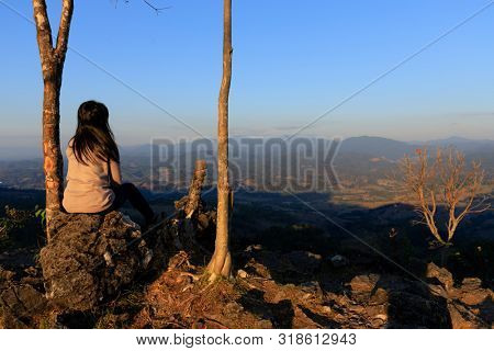 Sitting woman enjoying the landscape view from the Doi Hua Mod view point in Umphang province, Thailand