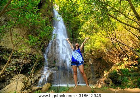 Happy woman outstretching her arms at the Thi Lo Su waterfall in Thailand