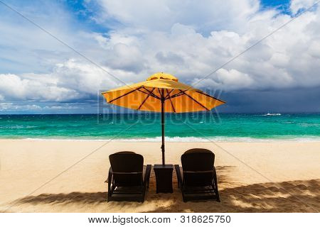 Sun Umbrella And Beach Beds Under The Palm Trees On Tropical Beach. Summer Vacantion Concept.